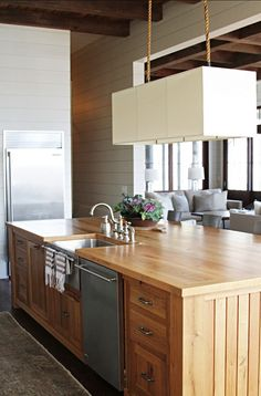 Yes to this - large kitchen island with sink. Like the deep sink w/stainless steel front and towel rack. Also like that it is NOT granite. Dishwasher right there is an asset. -S Designed by Yvonne McFadden LLC.