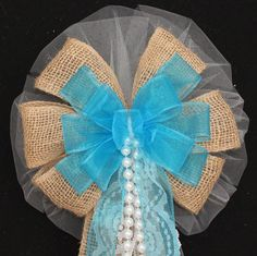 """This turquoise burlap wedding bow is the perfect combination of burlap and lace for a rustic theme wedding. The bow features lace tails and a pearl strand. Bow Details: - 8 loops of 6"""" white tulle (al"""