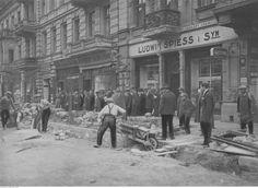 """Prace przy zakładaniu kanalizacji na ulicy Piotrkowskiej, przy budynku nr 107. Zwracają uwagę liczne szyldy, m.in. """"Domu Wiedeńskiego Maison de Vienne""""."""