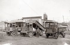 """1910. It shows three old dump trucks. The sign on the building and on the trucks reads """"S. M. Frazier"""""""