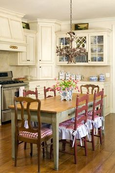 How to Achieve a French Country Style - This French kitchen pairs simple, smoothe, straight lines in furniture with more ornate finishing touches like patterned fabrics and chair ties.