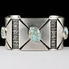 Hand stamped sterling silver bracelet with modernist medicine wheel plaques soldered over the stamp work and crowned with three natural #8 turquoise stones. Darrell Cadman, Navajo