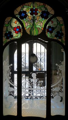 Art Nouveau etched glass doors, stained glass windows above