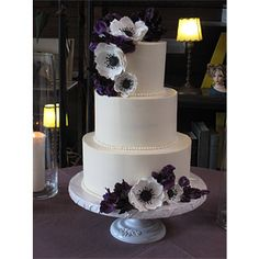 The cake will be topped with white anemones, purple hydrangeas and green seeded euchalytpus.  It will not cascade like this picture, but just be on top—simple.