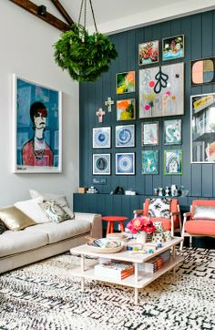 structured grid-like gallery wall on one end and a large oversized print on the other wall to balance it out. love the coral pink side chairs, dark teal accent wall and patterned moroccan rug. very lovely and comfortable eclectic bohemian living space.