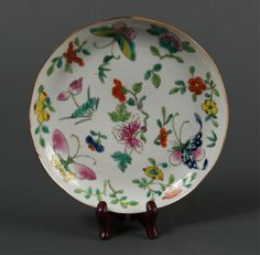 Chinese Famille Rose porcelain plate, 19th Century, of medallion shaped, finely painted with flowers and butterflies. Daoguang Marked on back. Wooden stand not included. D: 18 cm, 205 grams.