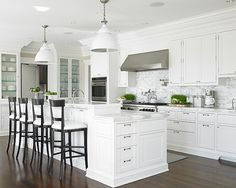White kitchen, white pendant lights, glass-front cabinetry
