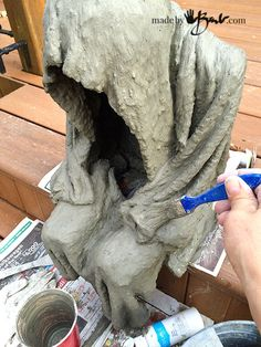 Make this simple concrete lighted step-spook with household waste and some concrete fabric draping. He is small scale and portable