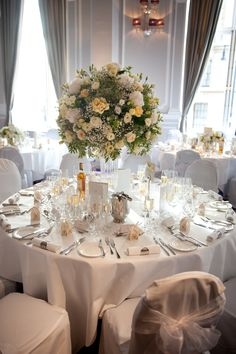 A Summery Yellow centrepiece with white chair covers. Flowers by 'By Appointment Only Design'