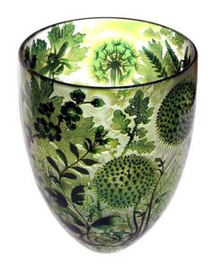 Dandelions in green, glass vessel.