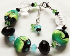 """Lampwork Beads & Crystal Bracelet  They are all in different shades of green with either white, green, turquoise, clear, or black accents. They are very elegant and pretty. IN addition to the LW beads I have added Austrian crystals and sterling silver beads. I have strung all of the beads on heavy, high quality stainless steel wire and added a good lobster claw closure.    The bracelet is a wearable 7.5"""" long, plus I have an extender so that it will fit most any size wrist. $12.99"""