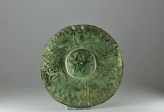 Luristan shield boss, 8th-7th century BC  Bronze of circular form, with raised center, the entire piece nicely adorned with incised and repousse relief of ibex, several holes for mounting to a wood shield, 14.6 cm diameter. Private collection