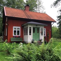 Torpet i juli. Fasaden är målad med ljusröd falufärg. Fönstren med linoljefärg…