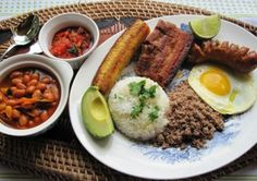 """Bandeja Paisa is probably the most popular Colombian dish, originally from the Andean region of the country where the people are called """"Paisas"""". Tradionally, bandeja paisa includes beans, white rice, chicharrón, carne en polvo, chorizo, fried egg, ripe plantain, avocado and arepa."""
