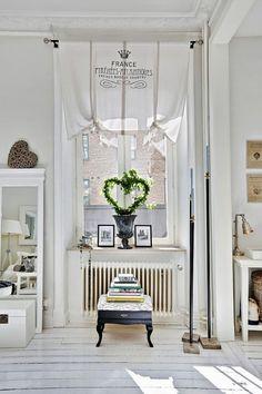 białe lustro stojące,wianek zielony w stylu prowansalskim,francuski ponóżek,czarna amfora,francuskie wazony gazony,wianek zielony dekoracyjny,rolety francuskie na oknach,francuskie drukowane rolety z napisami,białe rolety we francuskim stylu