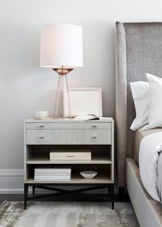 Elizabeth Metcalfe Interiors. White modern nightstand with black legs and storage www.bocadolobo.com