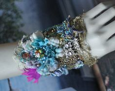 Romantic ornate wrist wrap inspired by splendor of baroque era; slightly asymmetric due of salvaged 1920 silk brocade piece used as base.Cuff is adorned with hand embroidered and beaded lace applique in shades of aqua and turquoise; embroidery with vintage colorful silk threads and handdyed wool, vintage ab diamante, vintage trims, crystals, dupioni silk and seed beading with bronze seed beads; fastens with a pair of latte color buttons; lined with silk. Measurements 18 cm wide with button…