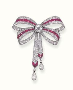 Ruby and diamond brooch designed as a calibré-cut ruby, old mine and old European-cut diamond ribbon bow, gathered by a collet diamond, to the ruby terminals and pear-shaped diamond drops, circa 1910