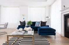 Chic living room features a sapphire blue velvet sofa with chaise lounge lined with black pillows facing a glass top cocktail table atop a black and white striped rug, Ikea Stockholm Rug.