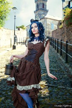 Steampunk in Brown and Blue Color Palette (brown and black striped dress, blue stockings/tights, train case purse, blue choker necklace, blue fascinator, blue hair in spiral curls)  - For costume tutorials, clothing guide, fashion inspiration photo gallery, calendar of Steampunk events, & more, visit SteampunkFashionGuide.com