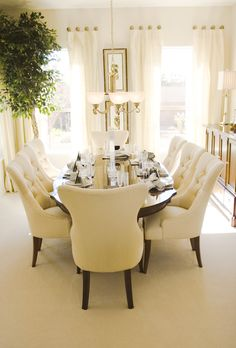 Bright sunny dining room with oval wood table and eight plush cream-colored dining chairs.