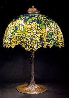 LABUMUM TABLE LAMP TIFFANY 1900-1910 POSTCARD    Labumum Table Lamp Loaded Favrile glass Tiffany Studios, New York.  Photo: J. Alistair Duncan Ltd.  Tiffany glass is the generic name used here to describe the many and varied types of glass developed and produced from 1878 to 1933 at the Tiffany Studios, by Louis Comfort Tiffany. However, it is his head designer until 1909, Clara Driscoll, who is the person now recognized as the real creator of the finest of the leaded glass Tiffany Lamps…
