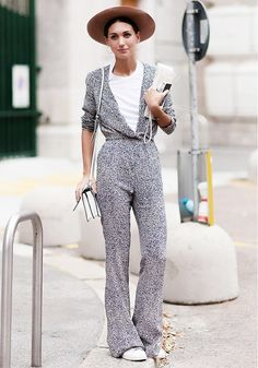 A white t-shirt is layered underneath a deep-v jumpsuit, paired with a felt hat, white shoulder bag, and sneakers