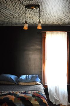 dark gray walls in a bedroom. I really like this. The window on the side sort of reminds me of Dorothy's bedroom at the end of the Wizard of Oz