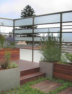 """privacy screen - smaller version for fence?"" ""metal privacy fence. The horizontal lines create an attractive motif in this modern rooftop garden, echoing the arrangement of the dark hardwood decking and planter boxes."" ""The privacy and opened of the surround"" ""Love the privacy that these screens/windows allow"" ""the frosted panels as a privacy screen are cool"""