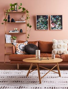 living room | brown leather sofa | couch | mid century | pink wall | artwork | shelves | decor | white rug | plants