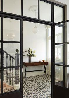 Hallway with tiled floor black and glass doors