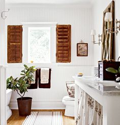 Classic, coastal remodeled bathroom with shutter window treatments, a skirted vanity, beaded board walls, and wood floors