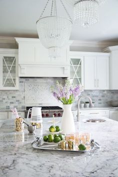 Gorgeous kitchen features a pair of beaded chandeliers illuminating an island topped with grey and ...