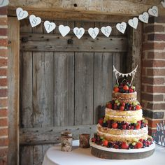 This naked wedding cake was the centre piece in the beautiful rustic Barn at Bury Court, Farnham. With a toffee sponge and salted caramel buttercream bottom tier, Victoria sponge with vanilla syrup bean buttercream and jam middle and coffee sponge with chocolate truffle top, this cake has a great selection to suit everyone's tastes. Finished with seasonal fruit.
