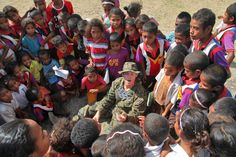 Hospital Corpsman shows children a card trick during a humanitarian mission at a remote village in East Timor.