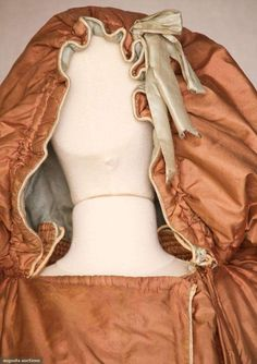 ladies hooded long silk cloak 1790sBrown tabby silk, channel quilted stand collar, 2 blue silk piped front arm slits w/ 3 blue silk covered buttons, oversized drawstring hood with oversized drawstring hood w/ blue silk lining outer bow & clock lining