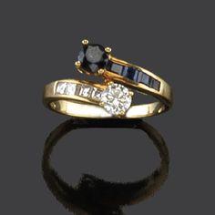 Anillo Tú y Yo con brillante y zafiro talla redonda en montura de oro amarillo de 18K con diamantes talla carré a los lados.  El brillante, aprox. 0,25 ct.
