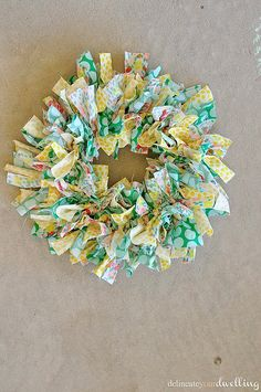 Create a summer wreath.  Small wire wreath frame from the craft store and strips of fabric tied to the wire.My first step was cutting all the fabric down to size.   Wreath form is  about 8″ in diameter,  Cut  fabric strips to be roughly 5″ in length and 1 1/2″ wide, tie them around the wire frame