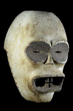 """Masque de la catégorie Téta-a-mokeba, c'est à dire """"le père des masques grotesques"""". Il apparait comme une entité antropomorphe mâle dans tous les rites des sociétés initiatiques du Ya-mwèi et du Kono. Ces rites concernent les jumeaux, les rites nocturnes du Bwete, les rites de passage, de mort, de deuil... Le bois mi-dur de Yombo et coloré d'argile blanc et de poudre de tukula (?). Voir exemple proche page 200 du livre """"L'esprit de la forêt"""" - ..."""
