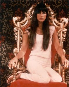 Cher sitting on her throne.