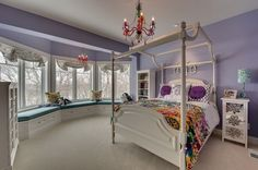 In this bedroom, the color layout of lavender and white with a little green to cheer up features a very feminine and peaceful girl's bedroom. The canopy bed, the arched window treatment and hanging chandelier make the room magical for a child.