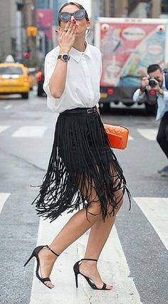 A Collared Shirt Tucked Into a Fringed Skirt With a Skinny Black Belt