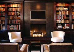 dark wood paneled library in a mansion with a fireplace, four armchairs, two white, two brown, built in book shelves full of books and a wall mounted tv