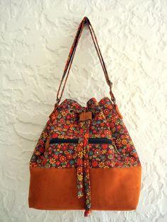 Bolsa Saquinho em tecido 100% algodão dublado , <br>com estampa floralzinha ferrugem <br>Fundo em camurça caramelo. <br> <br>Bolso frontal com zíper. <br>Forrada e com bolso interno. <br>Alça regulável <br> <br>Medidas: <br>altura: 32 cm <br>largura: 26 cm <br>profundidade: 15 cm Fashion Handbags, Fashion Bags, My Bags, Purses And Bags, Patchwork Bags, Cute Bags, Beautiful Bags, Purse Wallet, Evening Bags