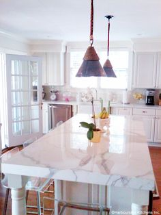 thick marble island table + pendant lighting in white kitchen by harbourside kitchens