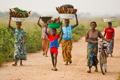 Democratic Republic of Congo: Women and children walking along a dirt road carrying produce to market in Kabalo.  ©FAO/Olivier Asselin  www.fao.org