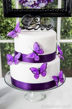 This white-and-purple wedding cake is topped off with a little love!