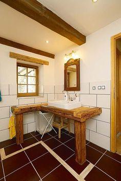 Ze dřeva jsou stůl pro umyvadlo i komoda.