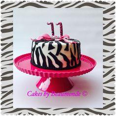 Zebrataart met roze strik met zebra reliëf en grote broche. Zebra cake with pink bow and brooche.