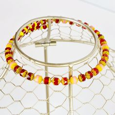 A regal combination of yellow-tipped red and pink cathedral cut Czech glass beads makes this memory wire choker a real standout. Wear it with bright colors or contrast it against basic black. You'll look great either way. Or give it to that special someone who likes to keep things light. This choker comes to a slight taper in the back, where it is finishedwith red glass bicones and bright yellow Czech glass bead caps. It's equal parts elegant and cute. Memory wire is easy to wear an...